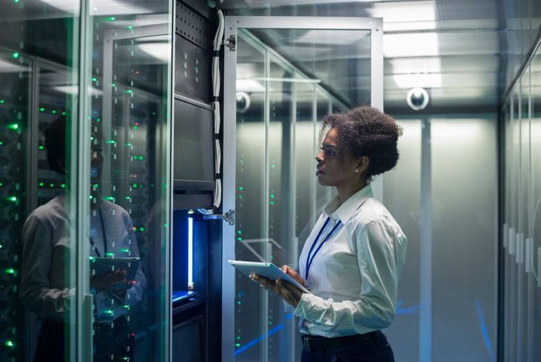 A female technician working on a tablet in a data center full of rack servers running diagnostics and maintenance on the system
