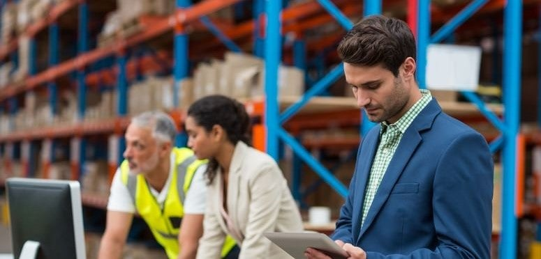 A male supply chain manager checking his notes while standing in a warehouse