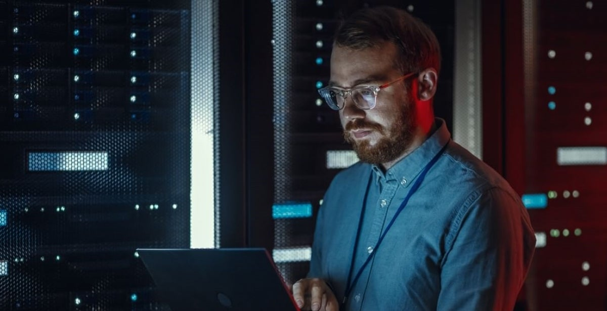 Bearded IT Specialist in Glasses is Working on Laptop in Data Center while Standing Near Server Rack