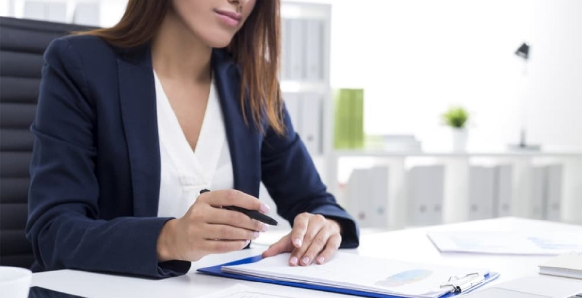 Business woman reviewing an employee complaint at her desk.